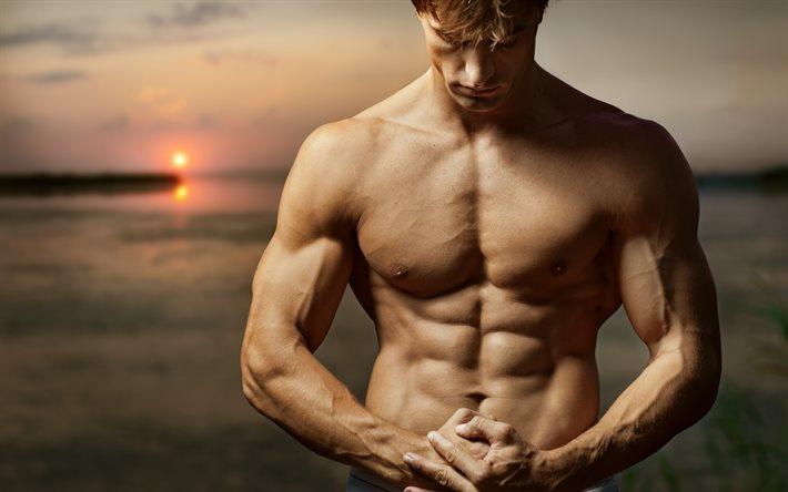 мускулистый мужчина на фоне заката