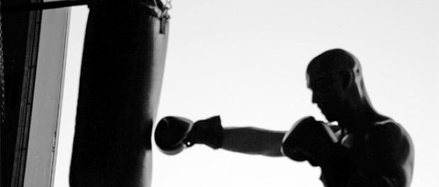 Силуэт лысого боксера, который бьет грушу