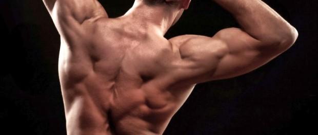Молодой человек с накаченными спинными мышцами позирует на черном фоне