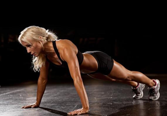 Блондинка в черной спортивной форме отжимается от пола