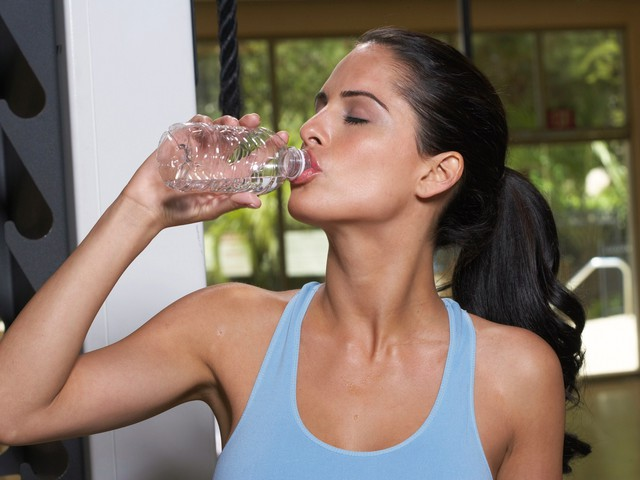 Woman drinking water in gym, eyes closed, close-up