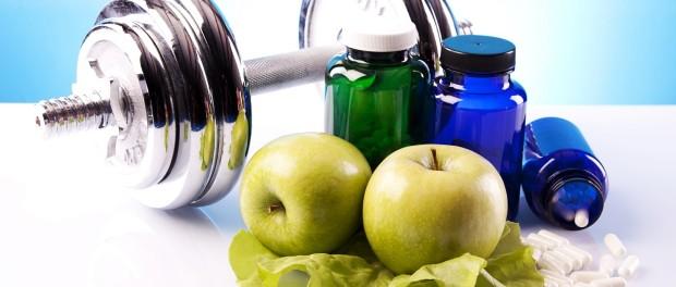 Яблоко, несколько пузырьков с таблетками, листья салата и гантеля