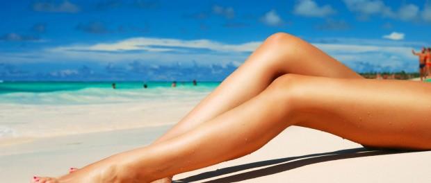 Стройные ножки на фоне голубого неба, пляжа и моря