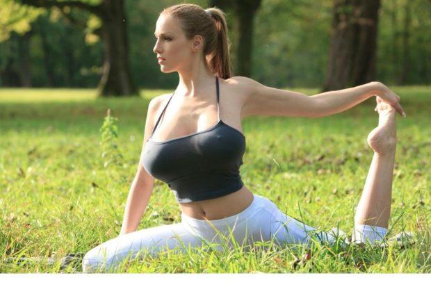 Девушка с пышной грудью занимается гимнастикой на зеленой травке в парке