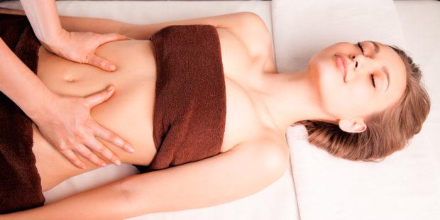 Девушка с блаженным лицом лежит на белой простыне в кабинете массажистки, которая массирует ее животик