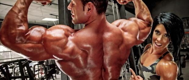 Мужчина демонстрирует накаченные мышцы спины и рук, женщина с огромными бицепсами стоит рядом и улыбается, показывая на спину мужчины указательным пальцем