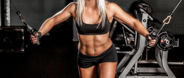 Девушка в спортзале качает мышцы рук