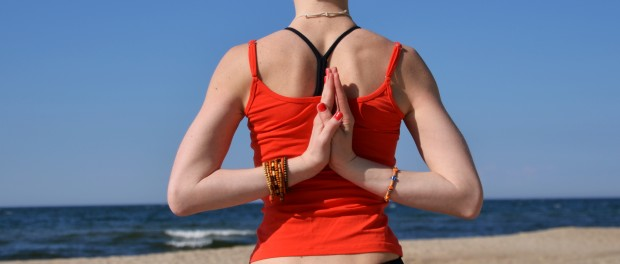 Короткостриженная девушка сидит в позе лотоса на берегу моря и держит руки за спиной