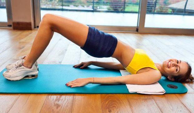 Улыбающаяся девушка демонстрирует правильное выполнение упражнения мостик