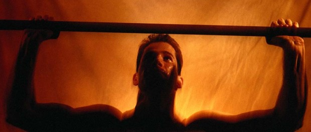 Фото в темно-оранжевых тонах, накаченный мужчина поднимает штангу широким хватом