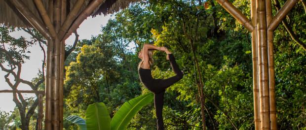 Девушка в черном спортивном костюме занимается йогой на огромной открытой террасе в джунглях, на фоне огромные деревья, пышные тропические кустарники, соломенная крыша и бамбуковые перекрытия