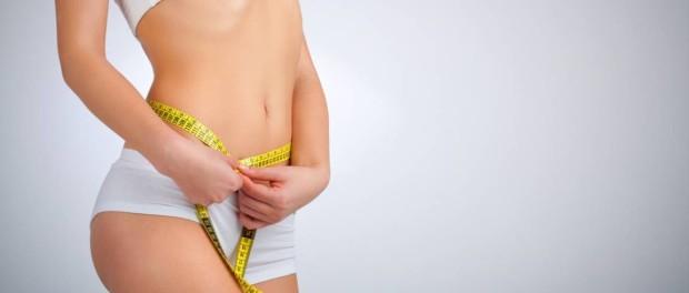 Девушка в белом нижнем белье с желтым сантиметром измеряет талию на сером фоне