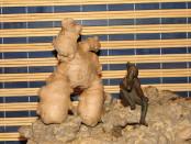 Корень имбиря странной формы напоминающей стоящего человека стоит на камне рядом с железной фигуркой задумавшейся девушка на фоне циновки