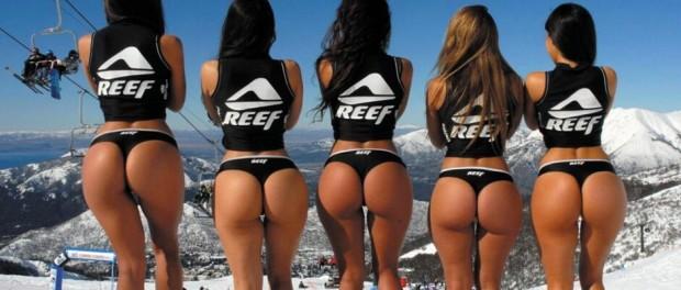 Красивые девушки в бикини и топах с надписью Reef на фоне горнолыжного курорта