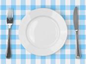 Белая пустая тарелка рядом с ножом и вилкой на бело-голубой клетчатой скатерти