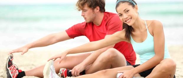Кудрявый парень и улыбающаяся девушка сидят на песчаном пляже и выполняют растяжку после бега