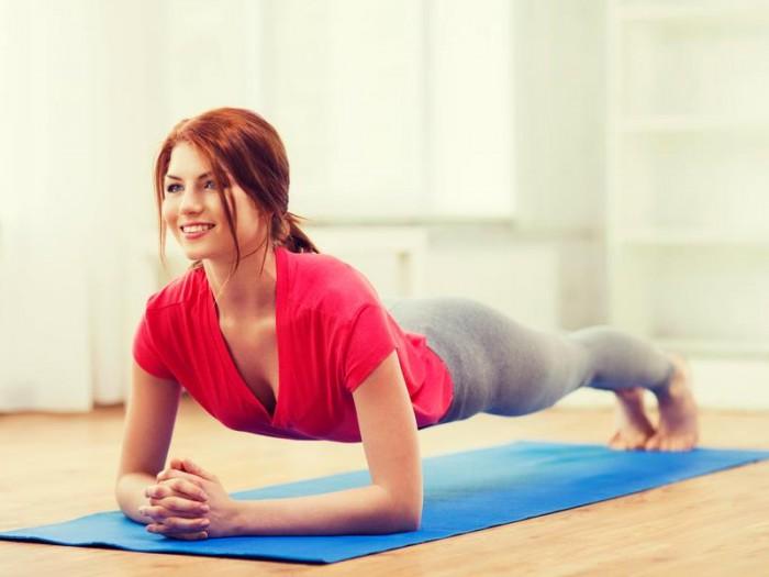 Рыжая девушка с улыбкой выполняет упражнение планка с упором на локти