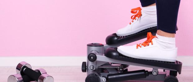 Девушка в белых кроссовках с оранжевыми шнурками стоит на механическом мини-степпере рядом с двумя небольшими гантелями на фоне нежно-розовых обоев