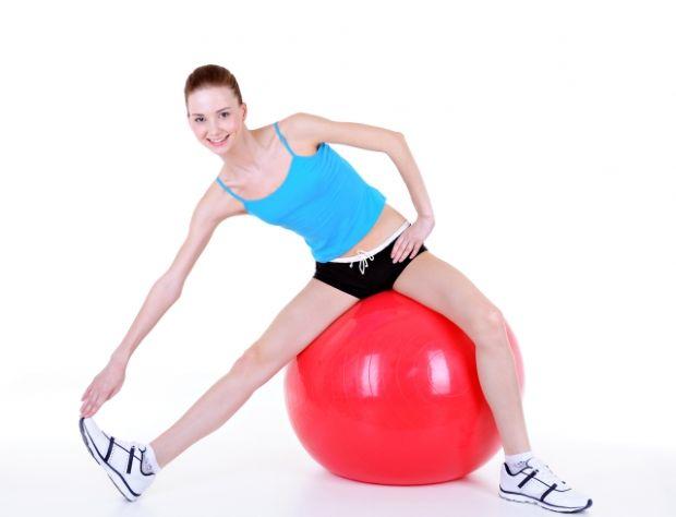 Девушка делает упражнения сидя на мяче
