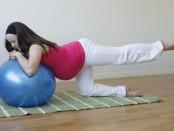 Женщина занимается гимнастикой в 3 триместре