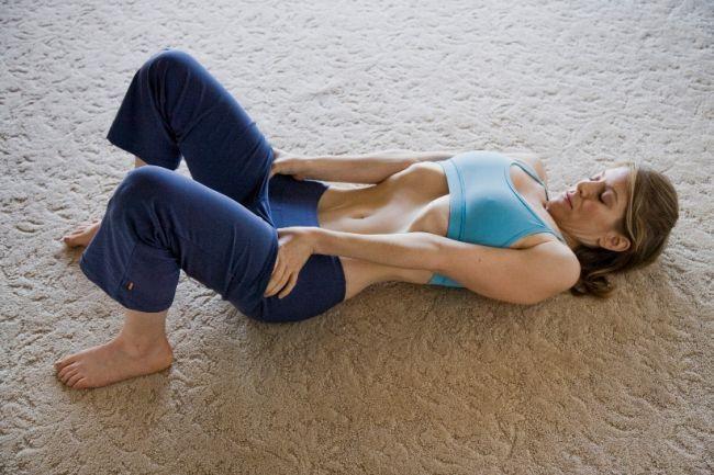 Девушка делает упражнение вакуум для плоского живота