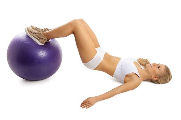Девушка делает упражнения для ног с мячом