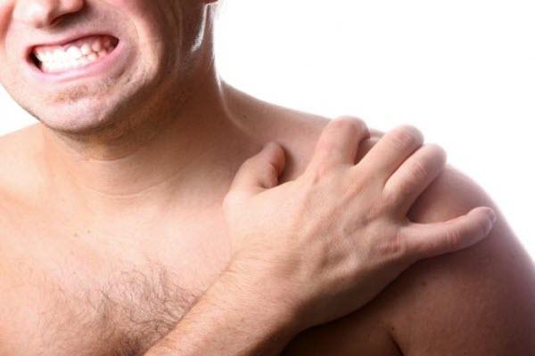 мужчина показывает больное плечо