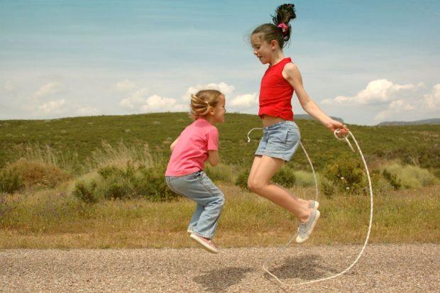 две девочки прыгают на скакалке на природе